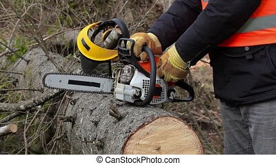 Lumberjack trying to start chainsaw