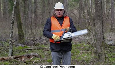 Angry lumberjack with chainsaw in forest