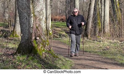 Hiker with walking sticks get pain in the leg