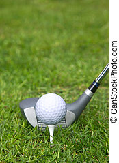 Tee\'d up - Golf ball on a tee with a driver in position.