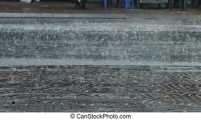 Rain Pattering on Street Pavement - Pan shot of rain...