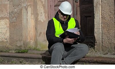 Building inspector sitting and checking documentation at the...