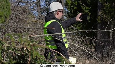 Lumberjack take picture on tablet PC at the pile of branches