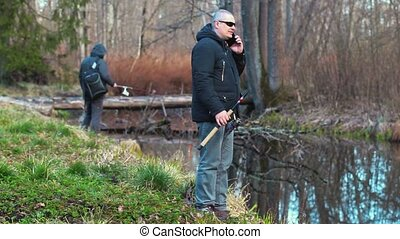 Fishermans with fishing rods and smart phone on river's bank