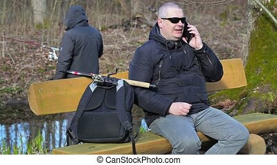Man with backpack and fishing rod sitting on the bench and...