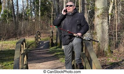 Man with fishing rod sitting on wooden bridge and talking on...