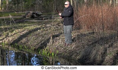 Man draw up fishing rod near river
