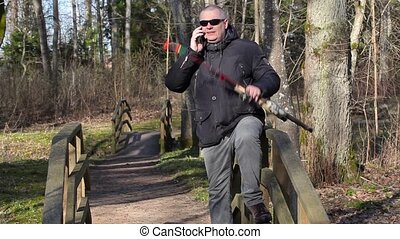 Man with fishing rod talking on smart phone and walking away