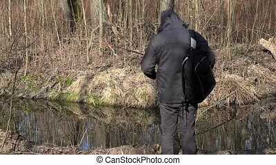 Male with backpack start fishing near river