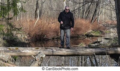 Men are fishing on log which cross the river