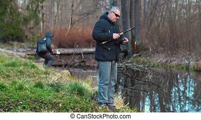 Fisherman draw up fishing rod on river's bank