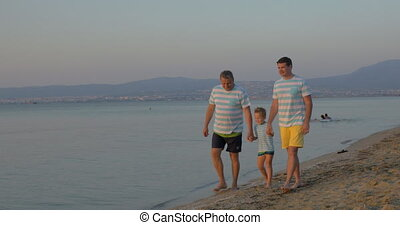 Child, father and grandfather walking on the beach -...