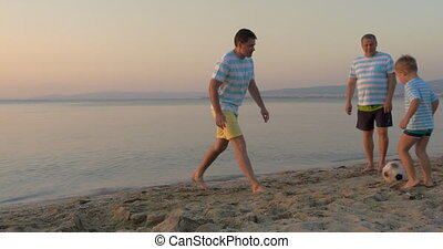 Men of three generations playing football on beach -...