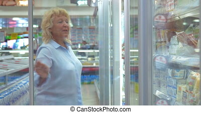 Woman buying food in fridge dairy section - Senior blond...