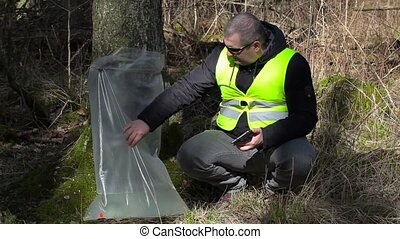 Forest Officer using tablet PC near tree with birch juice
