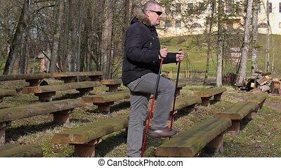 Hiker with walking sticks do exercises on bench in the park