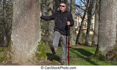 Hiker with walking sticks do exercises for legs near tree in...