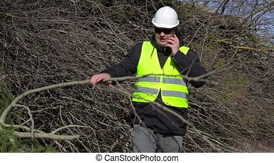 Lumberjack talking on cell phone near pile of branches