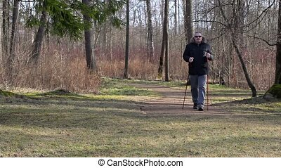 Hiker with walking sticks walking in the park