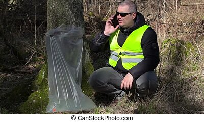 Forest Officer talking on smartphone near tree with birch...