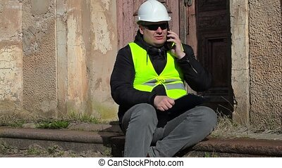 Angry Building inspector sitting and talking on smart phone