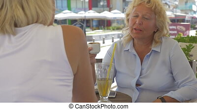 Senior women talking and having drinks in street cafe -...