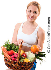 healthy eating - young woman holding basket of vegetables