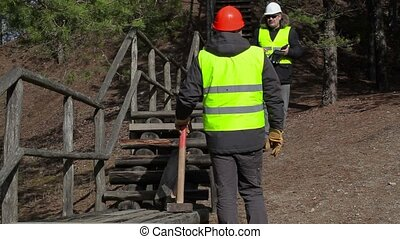 Worker explains the set task near to the broken wooden track