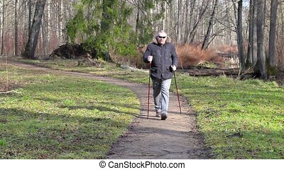 Tired hiker with walking sticks on path in the park