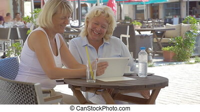 Women watching something funny on tablet PC in outdoor cafe...