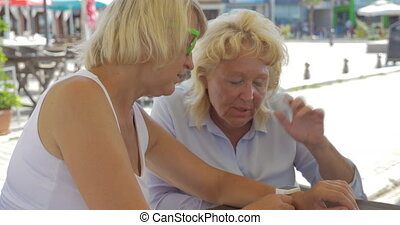 Senior women in street cafe using smart watch - Two women...