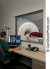 MRI Technician - Technician monitoring an MRI scan