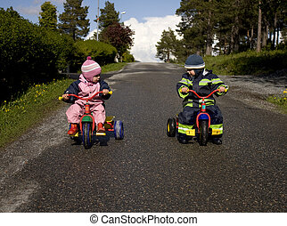 Brother and sister ready to race down a hill om tricycles