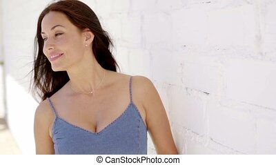 Smiling young brunette presses against white wall - Smiling...