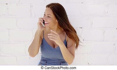 Smiling young woman talking on a mobile phone as she leans...