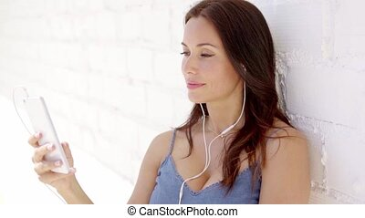 Attractive woman listening to music on earphones