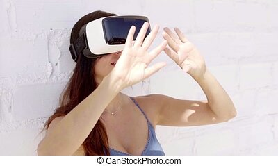 Young woman wearing virtual reality glasses walking along...