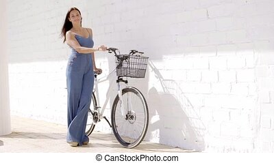 Elegant young woman holding a bicycle - Elegant young woman...