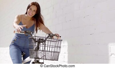 Friendly attractive young woman riding a bicycle