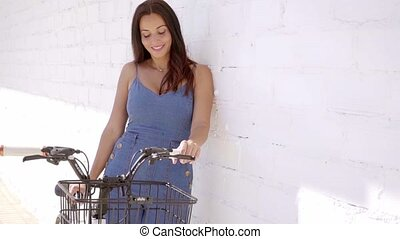 Attractive woman standing holding a bicycle as she leans...