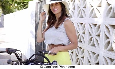 Smiling chic young woman holding a bicycle - Smiling chic...