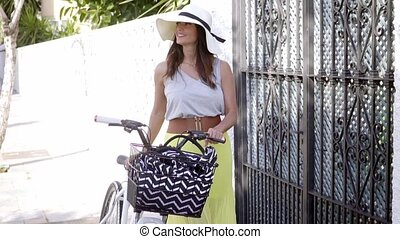Fashionable young woman standing with her bicycle