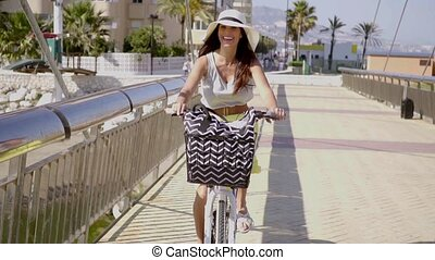 Pretty woman riding along a seafront promenade - Pretty...