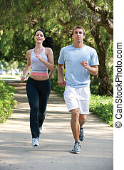 Jogging Couple - Attractive, young couple jogging in the...