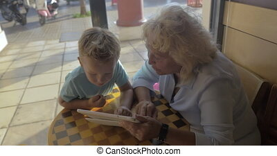 Child and grandma using tablet PC in cafe - Grandmother and...