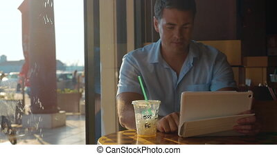 Man using tablet computer in cafe - Young man browsing the...