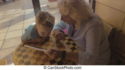 Boy and grandmother entertaining with touch pad in cafe -...