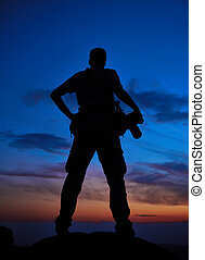 professional photographer silhouette at sunset or sunrise -...