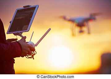 drone quadcopter flying at sunset - drone quadcopter flying...