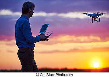 man operating of flying drone at sunset - Man operating...